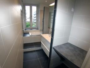 Espace machine à laver et sèche ligne à l'entrée de la salle de douche