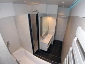 Salle de douche avec baignoire, lavabo double, miroir avec placard et sèche serviettes